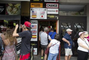 Turistas en uno oficina de cambio de moneda en Sevilla.